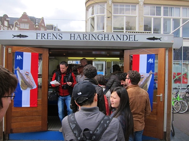 A typical outdoor herring stand in Amsterdam, with a line