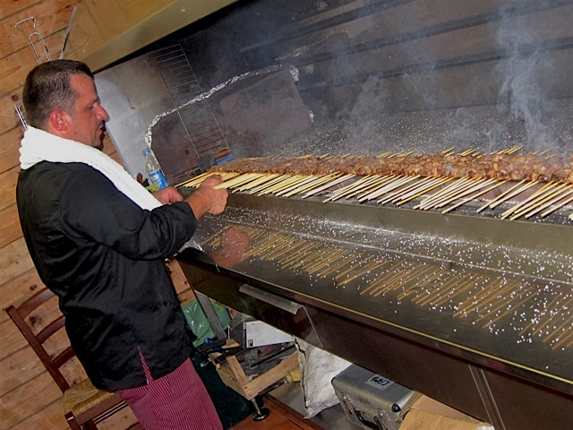 An arrosticini specialist working the grill