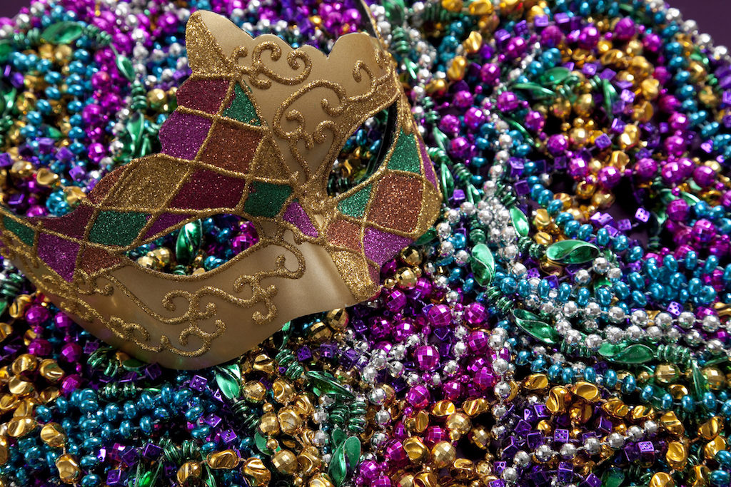 A group of Mardi Gras beads an mask with copy space