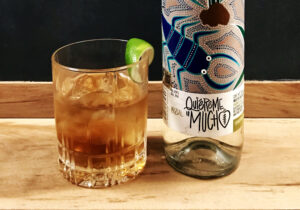 A_Darker_Shade_Mezcal_Cocktail_Recipe_Close_Up_with_Quiereme_Mucho_Mezcal_Bottle